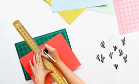 Cutting mat with hands holding a ruler while cutting a sheet of paper