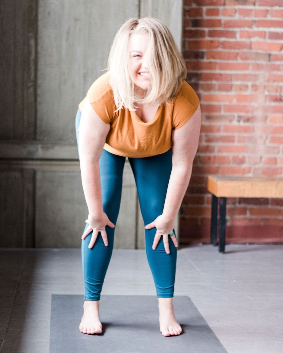 blonde woman standing on a yoga mat smiling with hands on knees