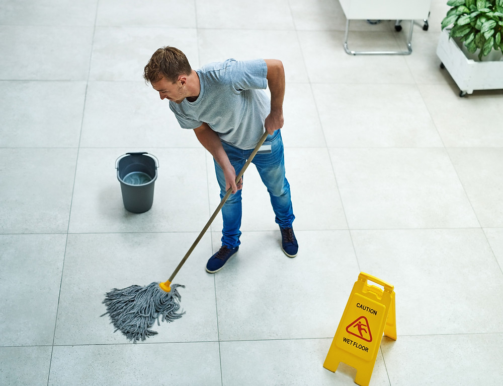 Young man mopping floor.