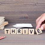 thrive. Wooden letters on dark backgroun