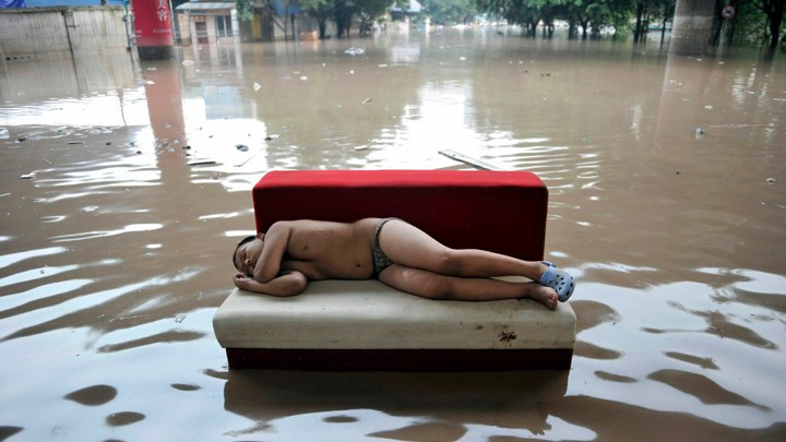 A child sleeps on a couch in a flooded street in Chongqing, China, on July 20, 2010