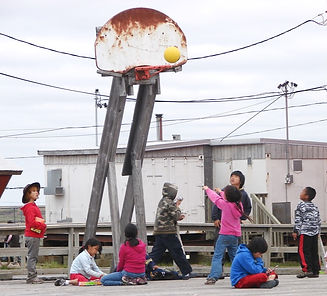 A group of children playing basketball in Kongiganak