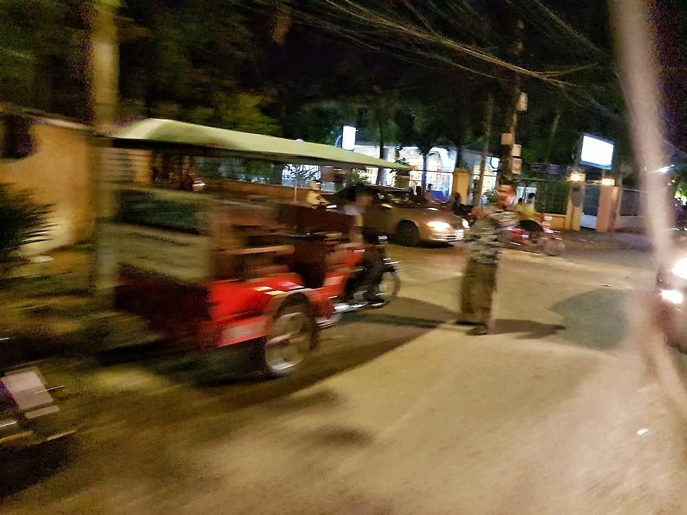 Tuk-tuk w ruchu na ulicy w Phnom Penh nocą