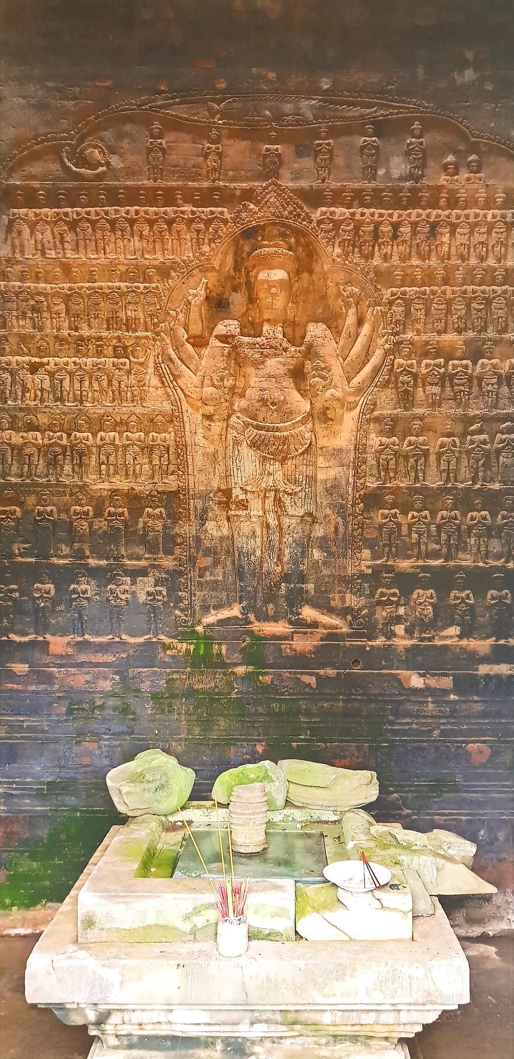Płaskorzeźba wielorękiego Siwy  w Angkor Wat z buddyjskim ołtarzykiem, Kambodża