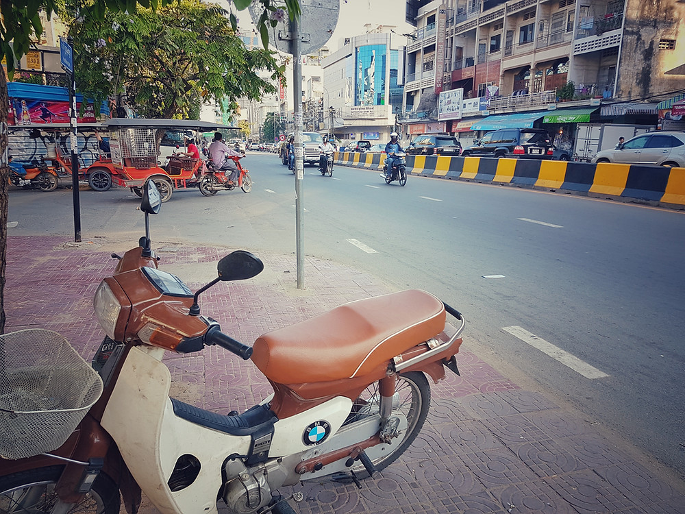 Motor BMW w centrum Phnom Penh na tle tuk-tuków na rogu alei