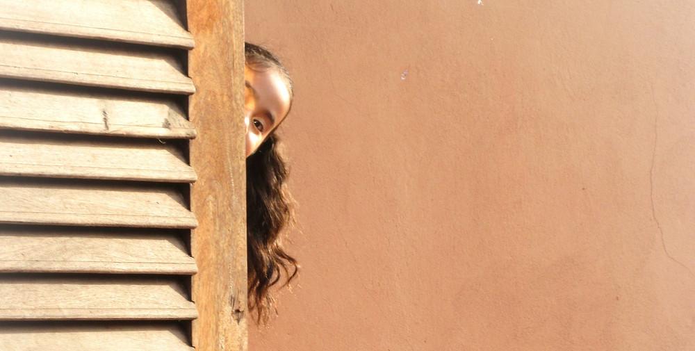 Dziewczynka z długimi włosami wygląda zza żaluzjowych drzwi, w tle pomarańczowa ściana