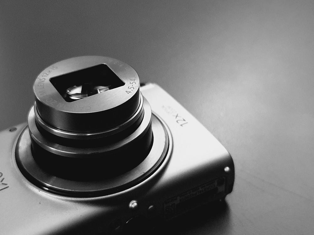 Automatyczny aparat fotograficzny z otwartym obiektywem na jednolitym tle, czarno-białe