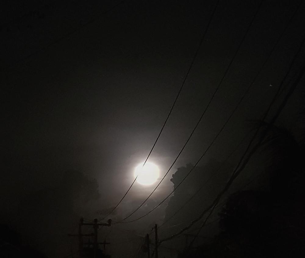 Księżyc na nocnym niebie w otoczeniu czarnych chmur