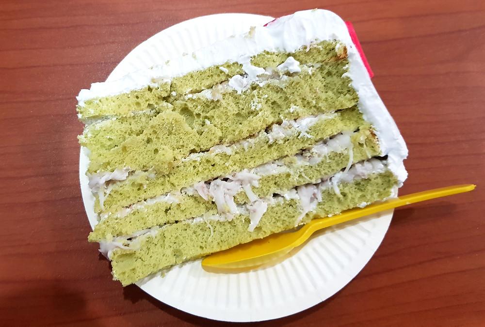 Kawałek tortu z zielonej herbaty i pulpą z miąższu kokosa, leży na papierowym talerzyku