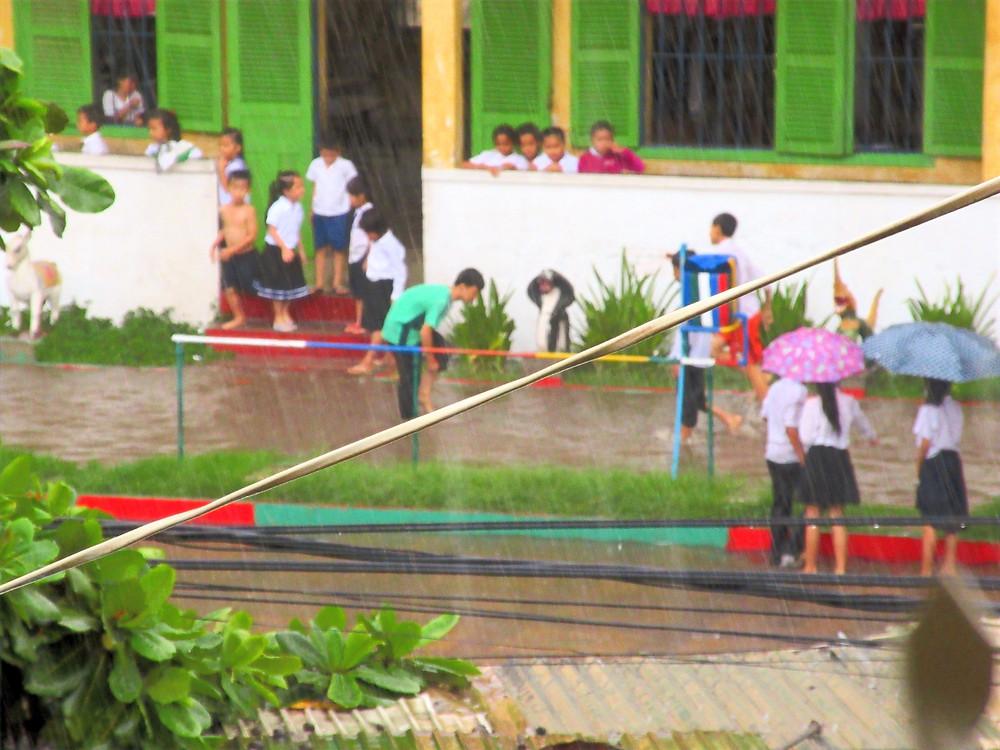 Rozmyte zdjęcie dzieci biegających w deszczu przed żółtym budynkiem szkoły, centrum Phnom Penh