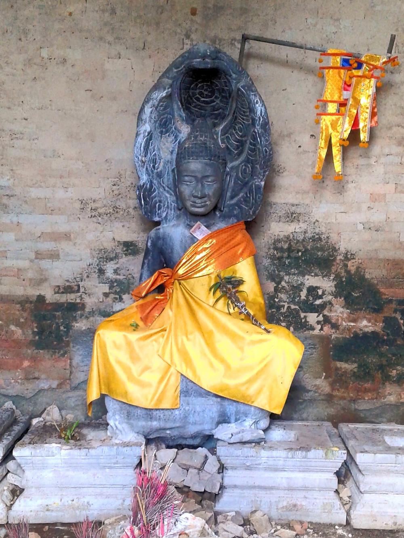 Siedząca statua Buddy okryta pomarańczową szatą, znajdująca się w starej, brudnej świątyni w Angkor Wat. Buddę chroni siedmiogłowy wąż Naga