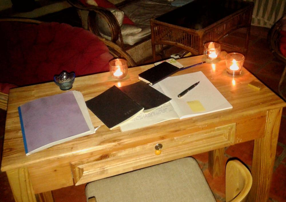 Zeszyty pisarskie i pióro leżą na drewnianym biurku, dookoła stoją zapalone świeczki, w tle fotele, stół i sofa