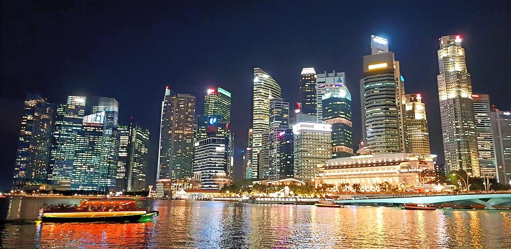 Widok drapaczy chmur i łodzi na wodzie w centrum Singapuru nocą