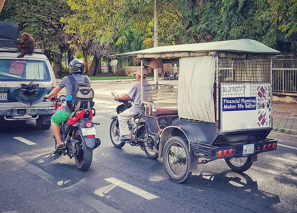 Tuk-tuk jadący ulicą a na samochodzie obok siedzi małpa