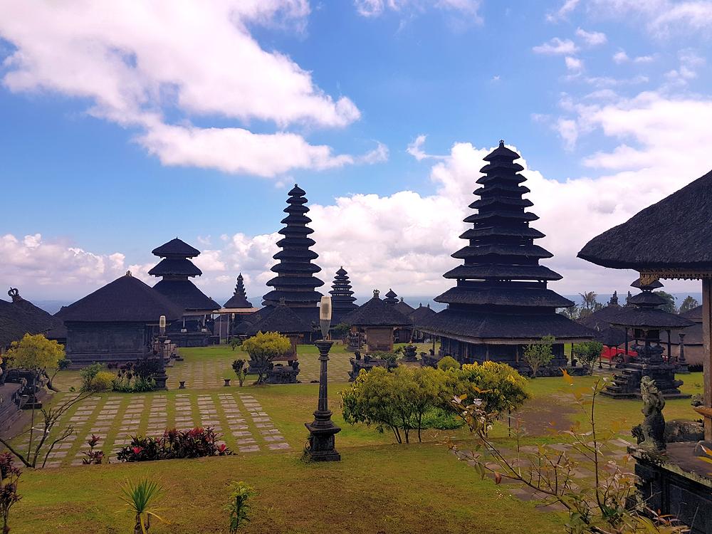 Besakih temple, świątynia na wyspie Bali w Indonezji, niebo, wieżyczki, chmury, zielona trawa oraz piękny pejzaż