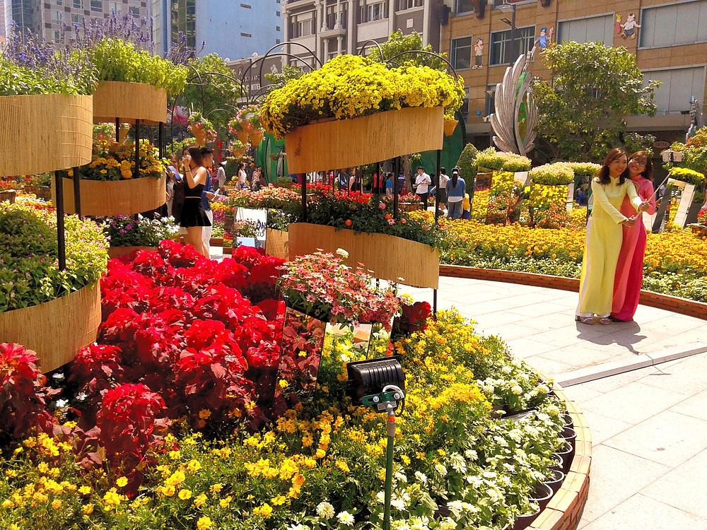 Festiwal kwiatów w centrum Sajgonu, Ho Chi Minh City, centrum miasta, kolorowe kwiaty w fantazyjnych formach, dwie Wietnamki fotografujące się