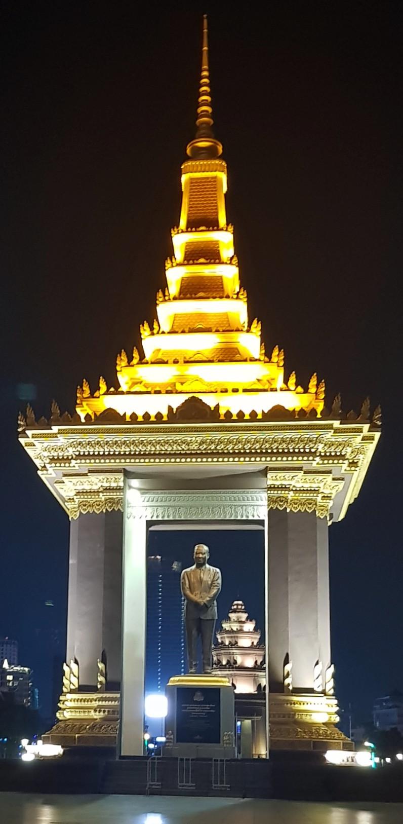 Pomnik króla Sihanouka Norodom w nocy oświetlony mocno światłem, na tle czarnego nieba, Independence Square Phnom Penh