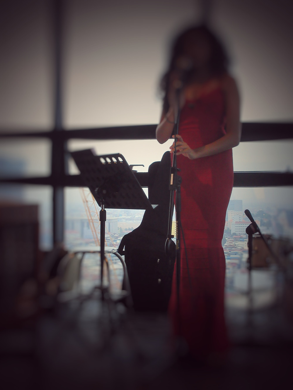 Zamazane. Długowłosa dziewczyna w czerwonej sukience śpiewa do mikrofonu na tle panoramy miasta za oknem