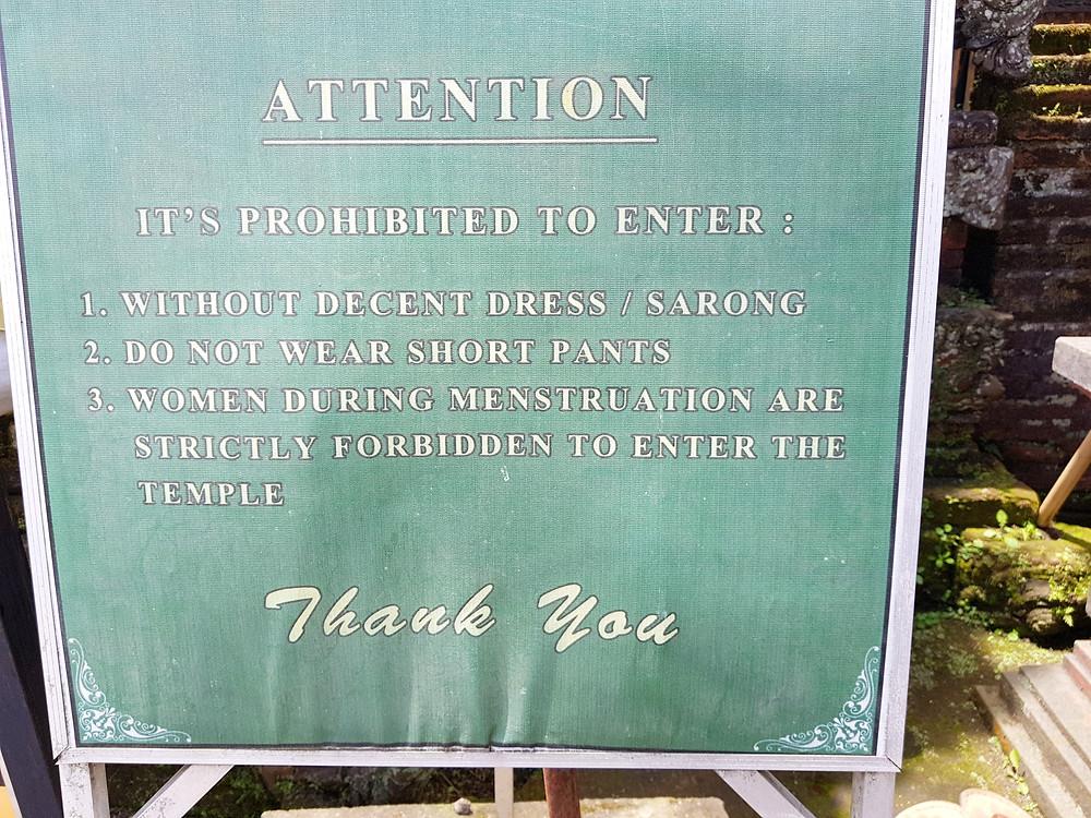 Zakaz wchodzenia do świątyni dla kobiet w czasie miesiączki w hinduistycznej świątyni na wyspie Bali. Zielona plansza z ogłoszeniem białymi literami.
