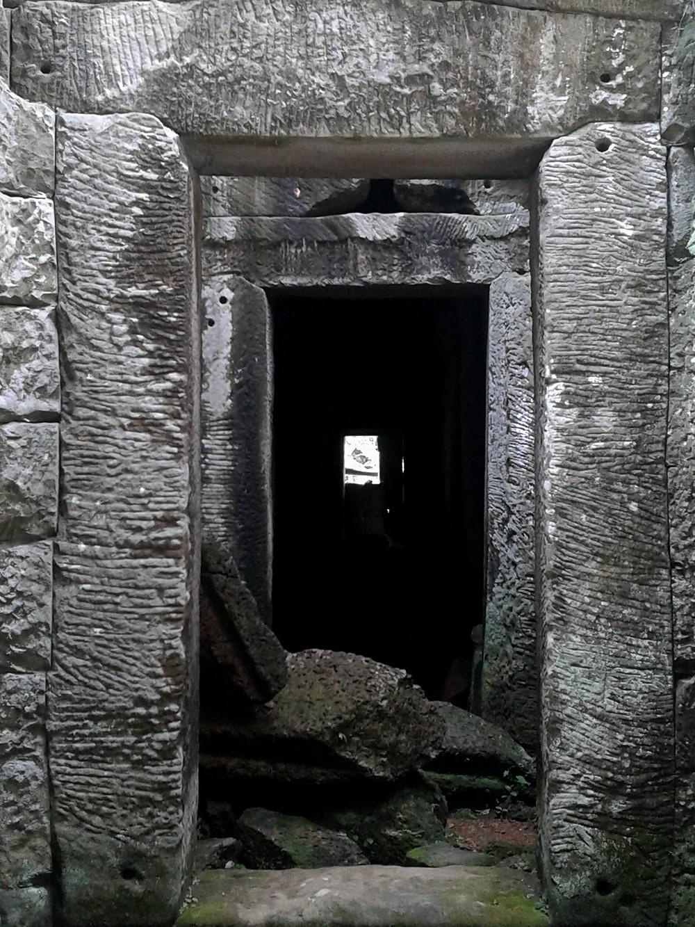 Widok długiego, czarnego korytarza zakończonego światełkiem w tunelu, świątynia Angkor Wat, Ta Prohm, Kambodża