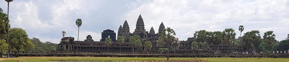 Widok panoramiczny frontu świątyni Angkor Wat w Kambodży, palmy i lekko zachmurzone niebo
