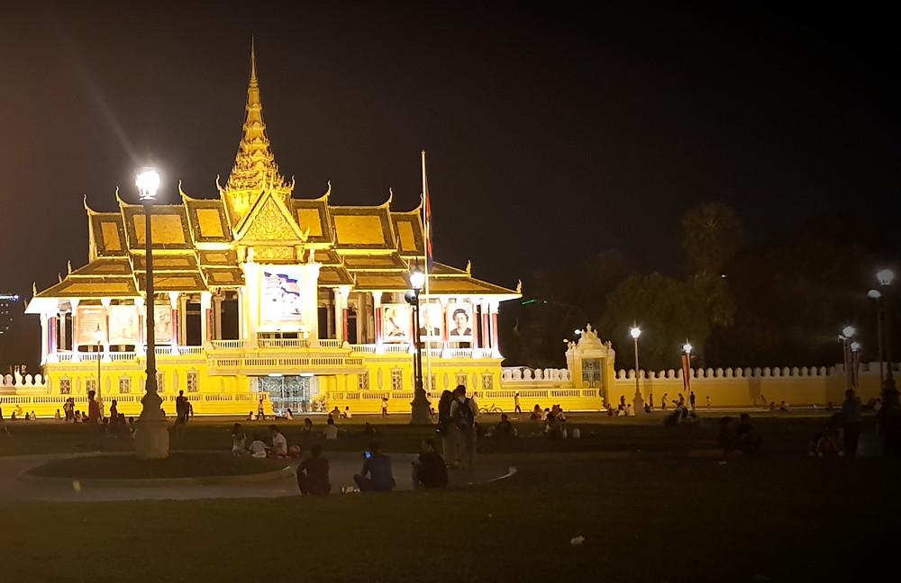 Pałac Królewski w Phnom Penh przy Riverside, złoty pałac mocno oświetlony na tle czarnego nieba w nocy, ludzie siedzą wokół pałacu