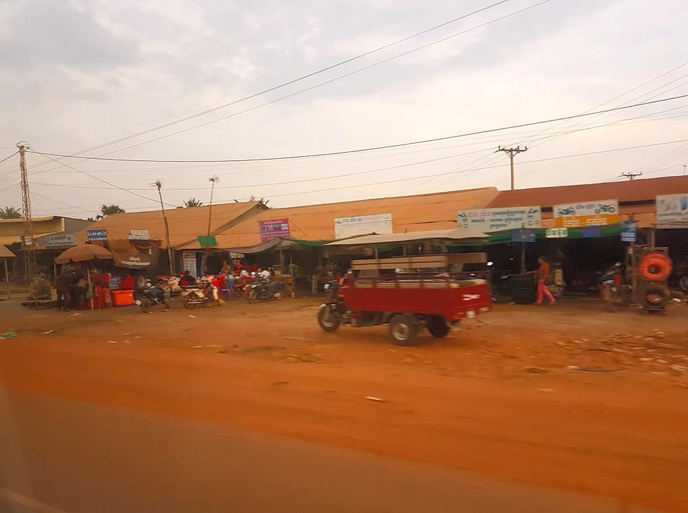 droga w Kambodży, tuk tuk, czerwona ziemia, sklepy, baraki, targ