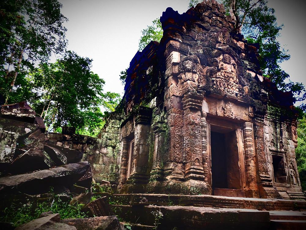 Ruiny budynku w Angkor Wat otoczone rozsypanymi kamieniami i dżunglą