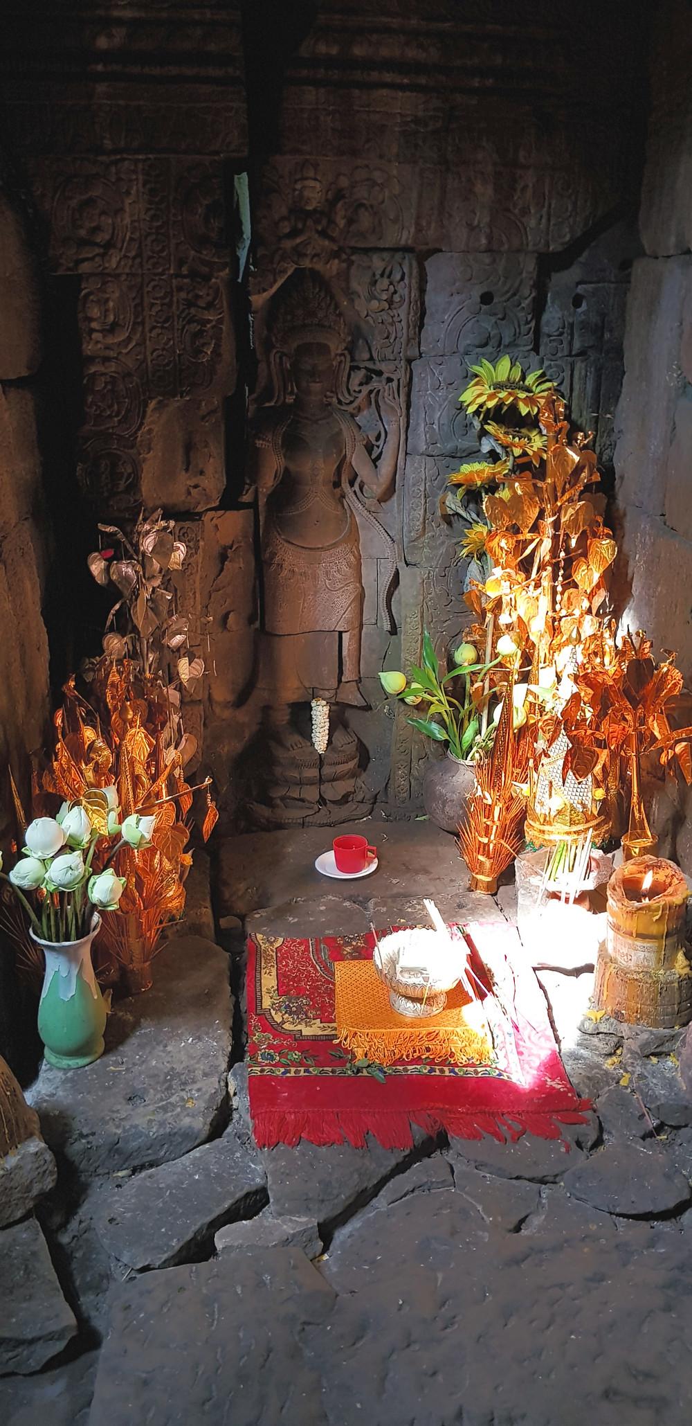 Angkor Wat, Kambodża, mała kapliczka z kwiatami lotosu, ozdobami, płaskorzeźbą appsary, dywanikiem na kamiennej podłodze, złotymi modelami roślin