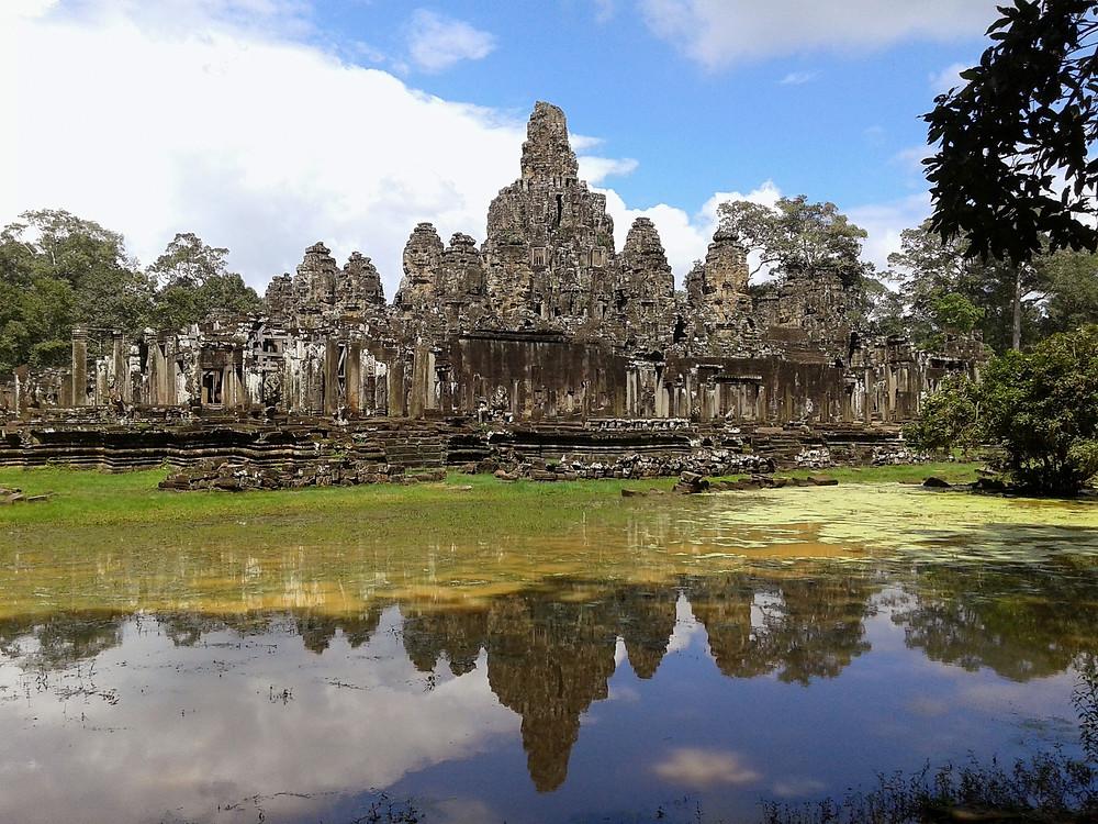 Świątynia Uśmiechniętego Buddy Bayon w Angkor Wat, błękitne niebo, chmury, odbicie świątyni w wodzie
