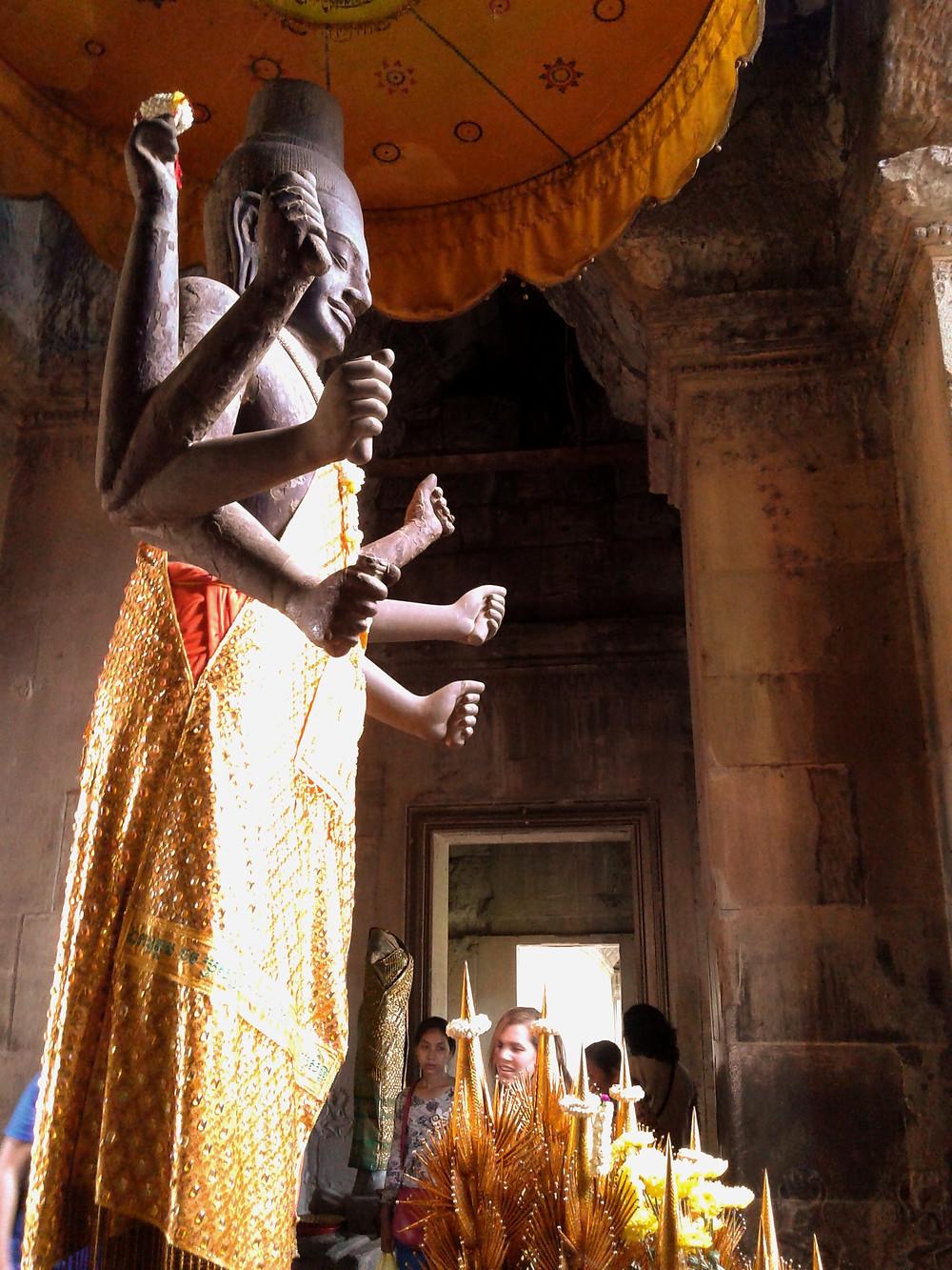 Posąg boga Siwy, Sziwy, Shiva w Angkor Wat, ośmioręki posąg stoi pod pomarańczowym parasolem i ubrano go w pomarańczowe szaty. W tle są kamienne ściany