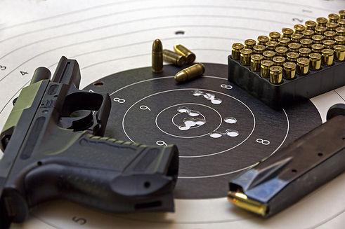 gun and ammunition over bulls eye score.