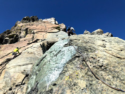 a view up a rock face with two rock climbers