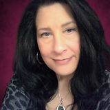 This image is of Kristina Hallett, owner of Mystic Rose Magick. An attractive 50 something year old white woman with blue eyes and raven black hair.