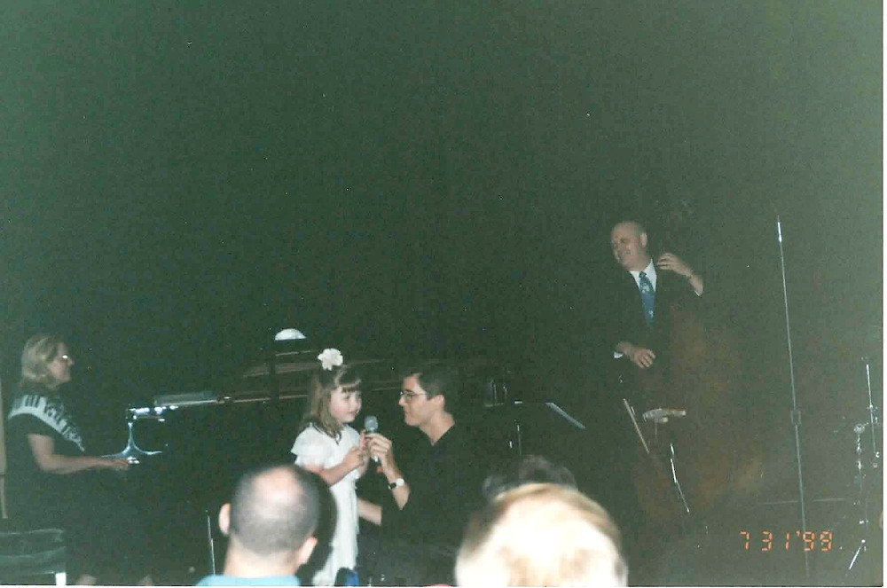 copy of a physical picture.  It shows 6 year old Anna with her Uncle Danny with a microphone singing with a piano player and bass player behind.