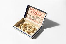 A string of broken vintage pearls in a prescription box