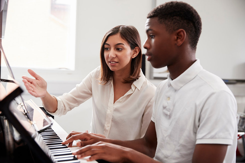 male-pupil-with-teacher-playing-piano-in