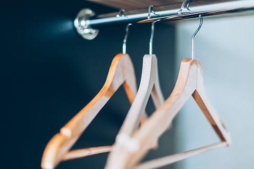 empty-wooden-hangers-on-rail-in-closet-Z