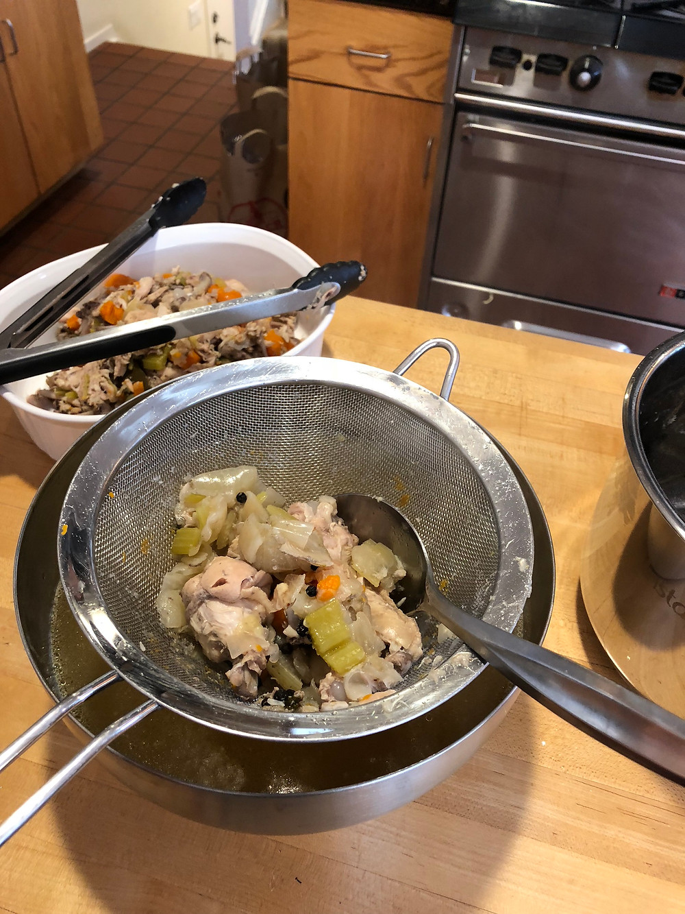 If you doing this right after the pressue naturally release keep in mind that everything is still very hot. Scoop out some of the vegetables and chicken and place in the strainer. Carefully, pour the broth thru the strainer ...remember it's hot!  Keep the golden broth and discard everything else.