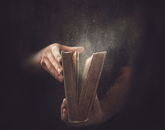 holding-an-open-book-with-dust-coming-ou