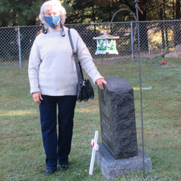9. Barb Wood places a cross on her husband's gravesite in St. Anthony's Cemetery.jpg
