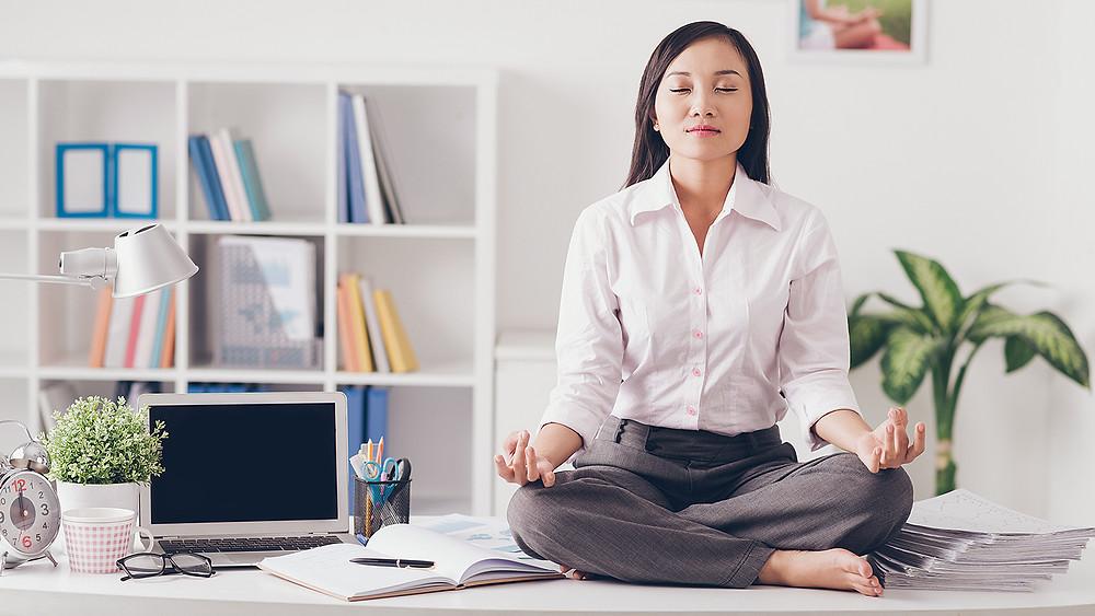 Una mujer sentada encima del escritorio con ropa de trabajo haciendo meditación yoga