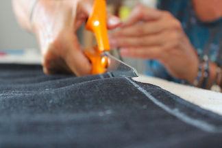 Gros plan sur la découpe d'un tissu destiné à un sac à main au sein de l'Atelier 3 Fois Oui