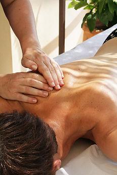 Gros plan sur les mains de la Thalassothérapeute entrain de masser le dos d'une femme