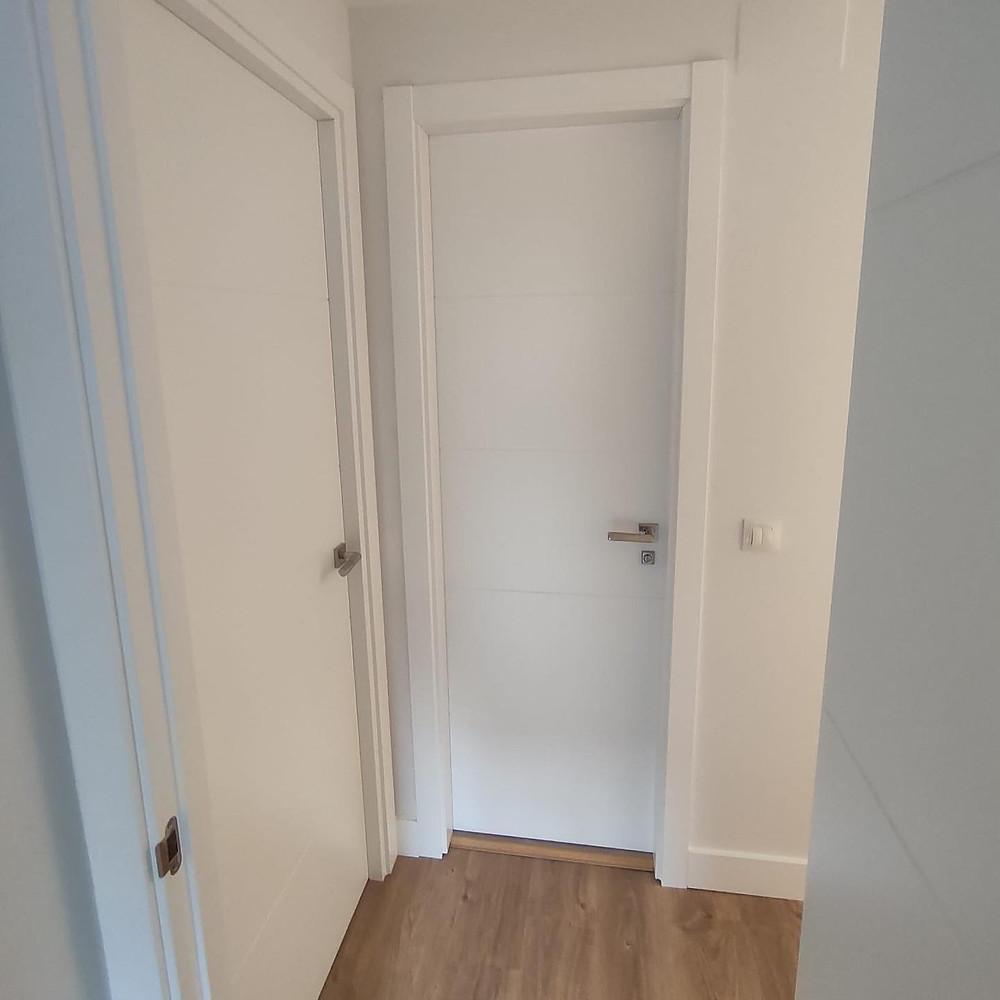 Puertas de interior lacadas en blanco en modelo 9005, 4 rayas, con herrajes en acero inox