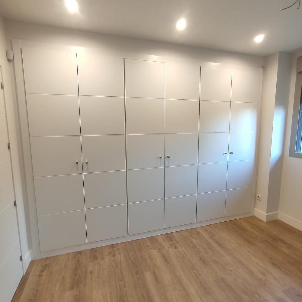 Puertas de interior de armarios abatibles en modelo 9005, 4 lineas, lacadas en blanco, con tiradores tipo bola en acero inox.
