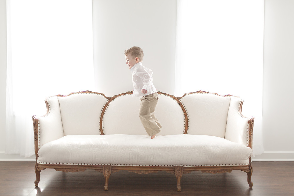 toddler boy jumping on a couch