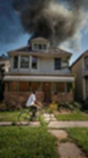 man riding bioke past a fire.jpeg