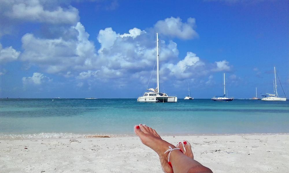Pies de mujer en las playas de Aruba. Arena blanca y el mar turquesa caribeño. Viajando barato a Aruba