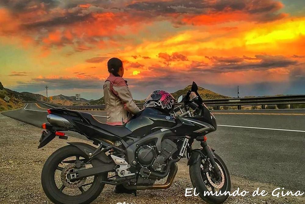 Mujeres que viajan solas por el mundo - mujer con motocicleta mirando atardecer